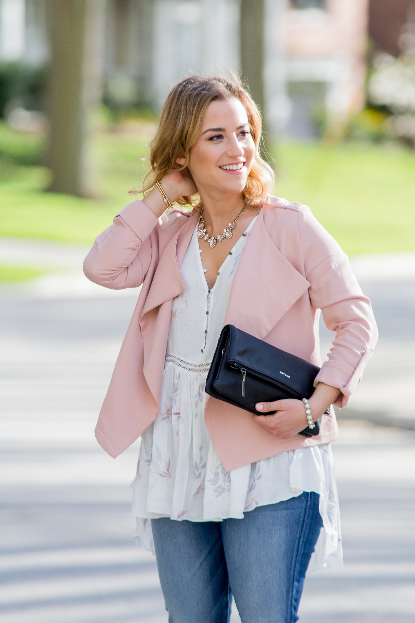 Chic and casual summer outfit idea, with a pink jacket, printed blouse and step-hem jeans