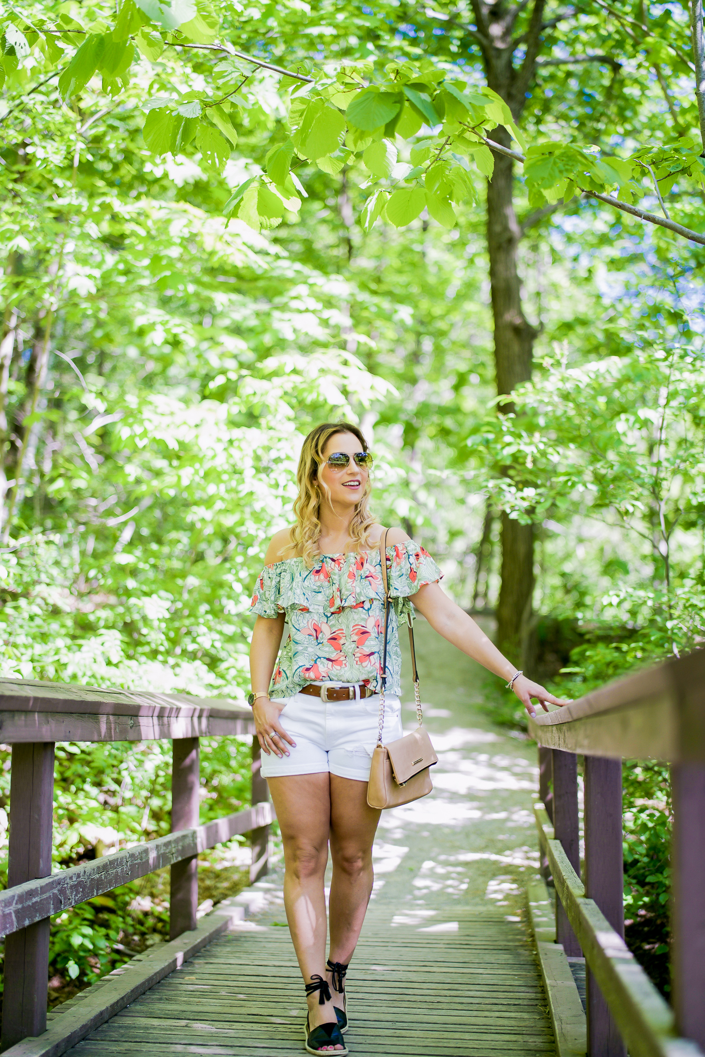 summer outfit idea, featuring a floral print off-the-shoulder top and boy fit ripped white denim shorts from GUESS