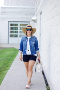 Casual and chic summer outfit idea, wearing a denim jacket with a white t-shirt, black denim shorts and oversized sunglasses