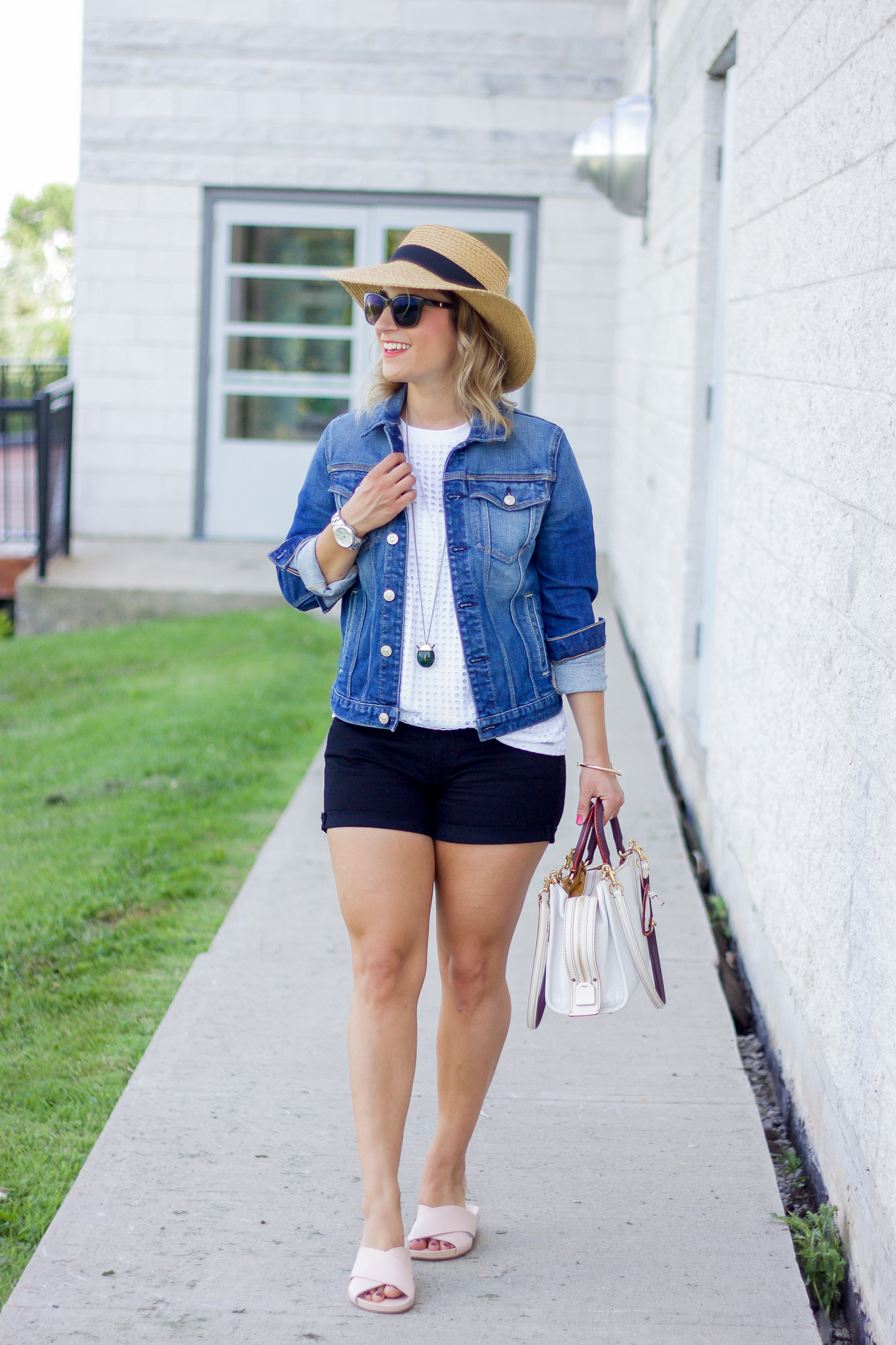 Summer outfit by petite fashion blogger, Jackie of Something About That, wearing black denim shorts with a jean jacket, textured white t-shirt and oversized hat