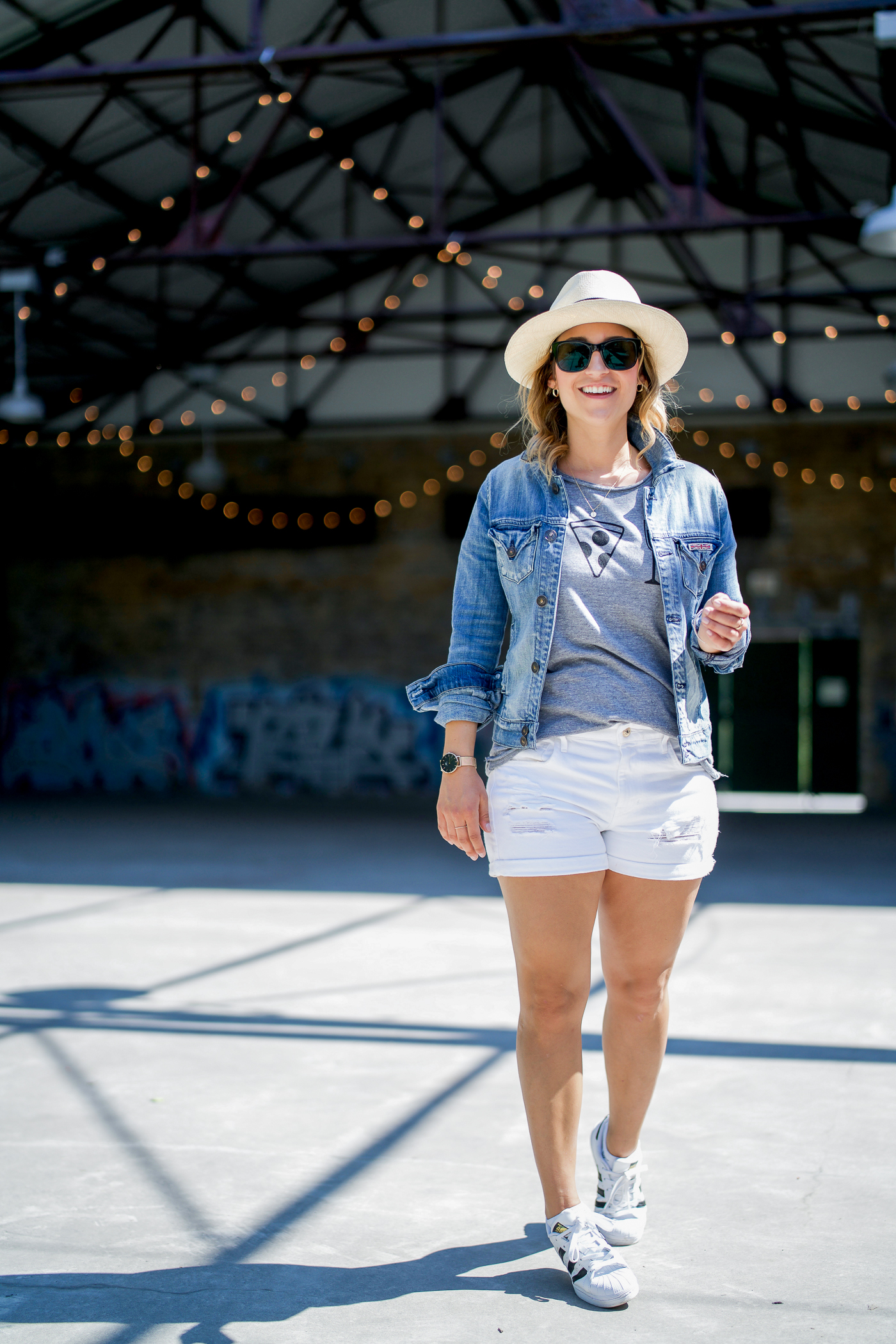 Simple casual summer outfit idea, wearing a Chaser Brand graphic tee with White Shorts at a denim jacket