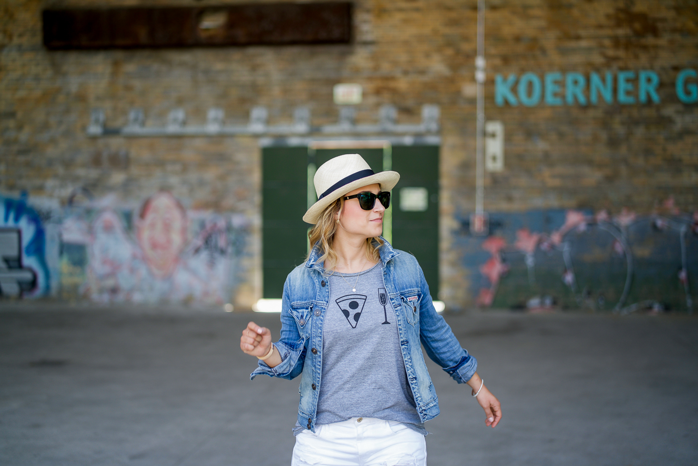 Jackie is a Canadian fashion and lifestyle blogger and she is wearing a Chaser brand daily riturals graphic tee with a jean jacket and straw hat
