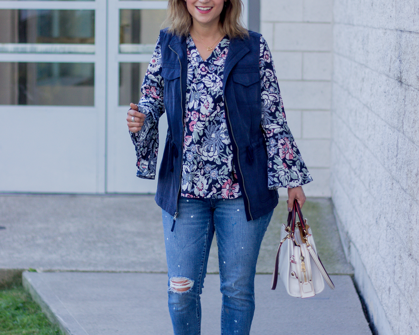 Summer to fall outfit idea, wearing a dark floral bell sleeve top from Amazon and a Merona vest with ripped jeans