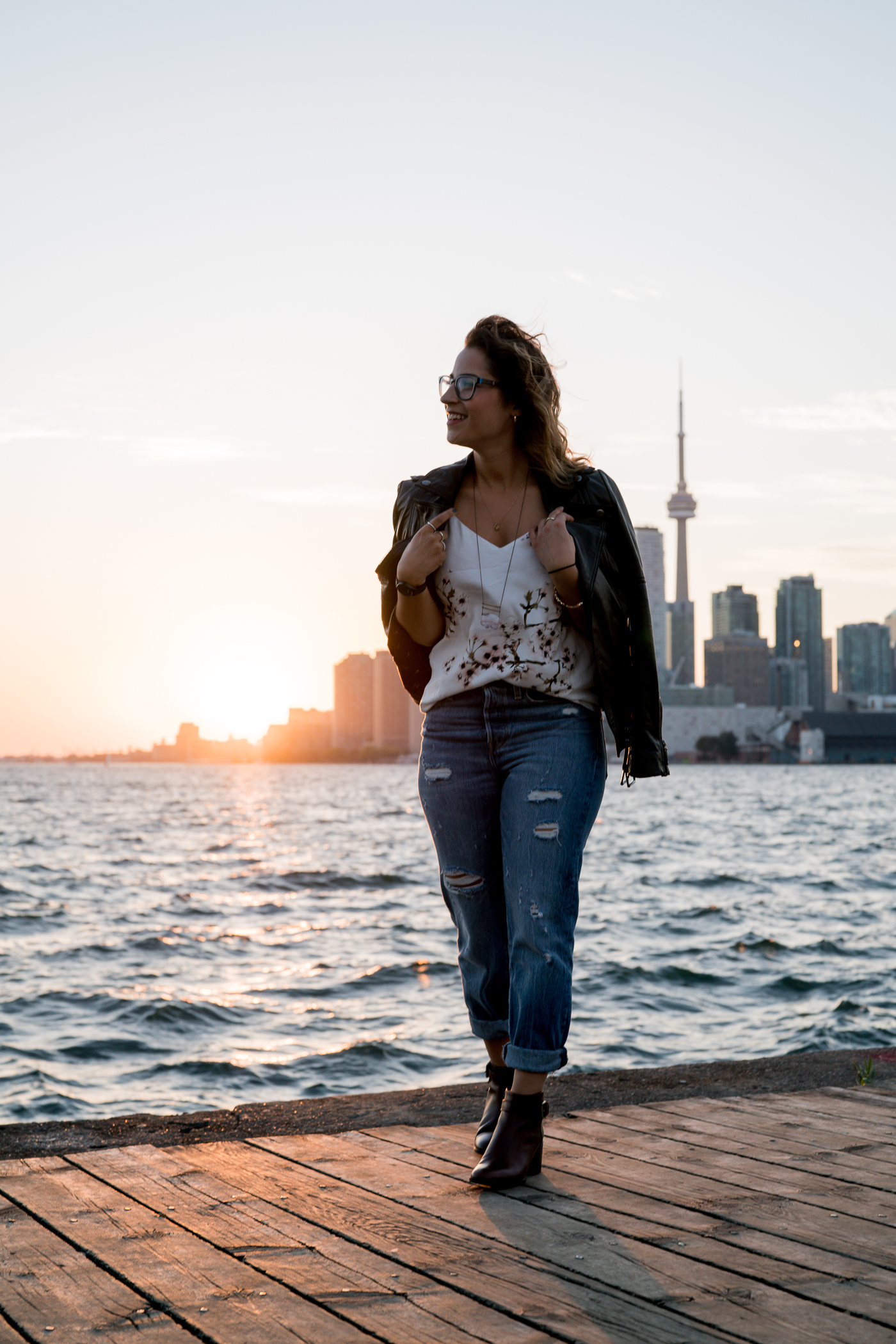 Canadian fashion blogger is wearing a black leather jacket with levi's wedgie jeans and a floral top