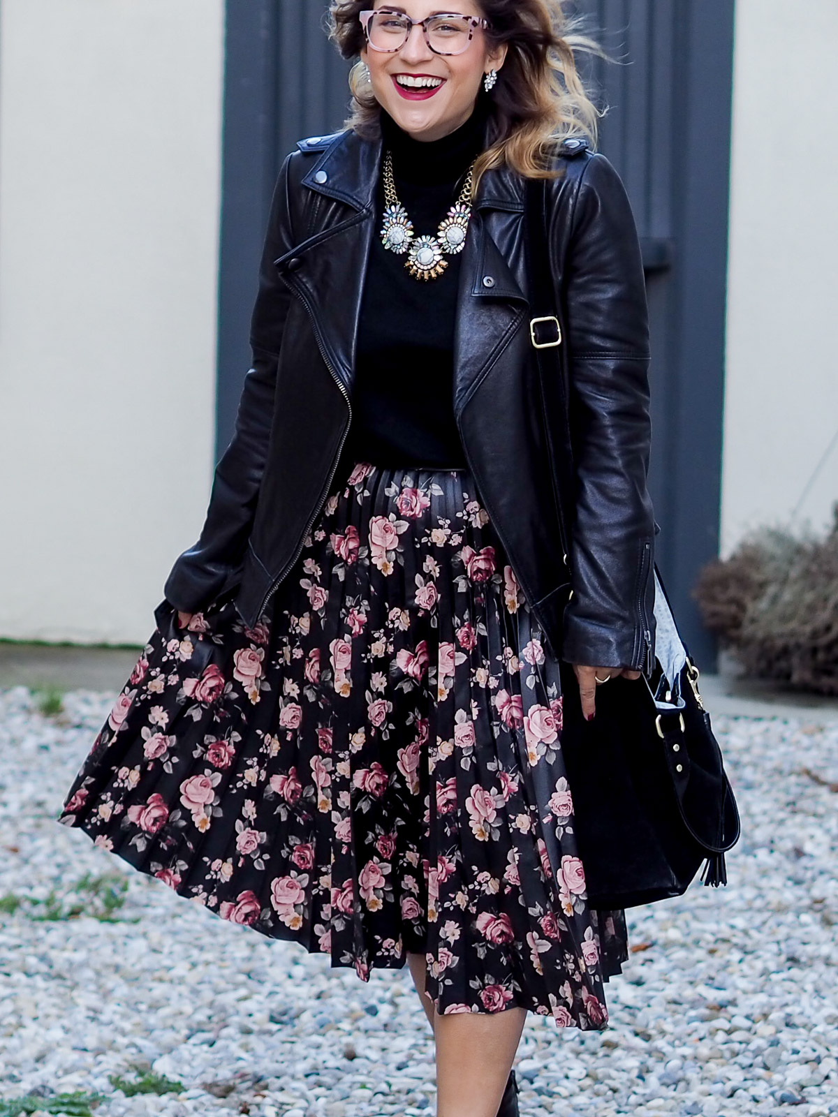 Edgy and chic holiday outfit! A cute pleated floral skirt with a black turtle neck sweater and edgy moto jacket.