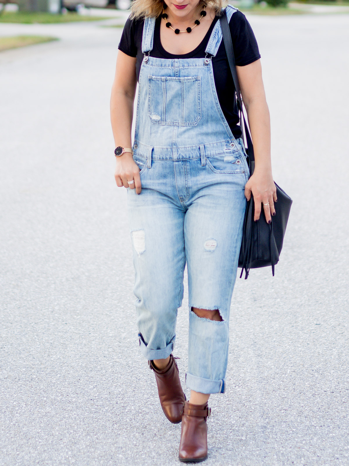 Ripped overalls with ankle booties and a basic black t-shirt