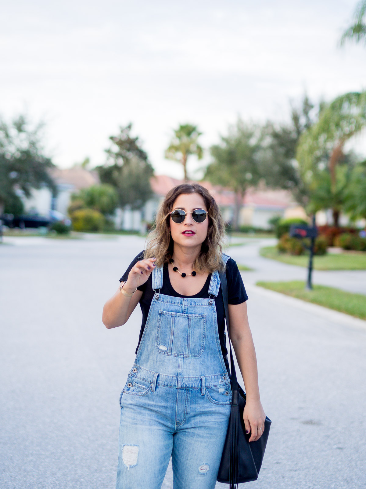 Toronto petite fashion and lifestyle blogger, Jackie from Something About That, wearing ripped overalls from Lucky Brand with a simple black tee and a pom pom necklace from Madewell