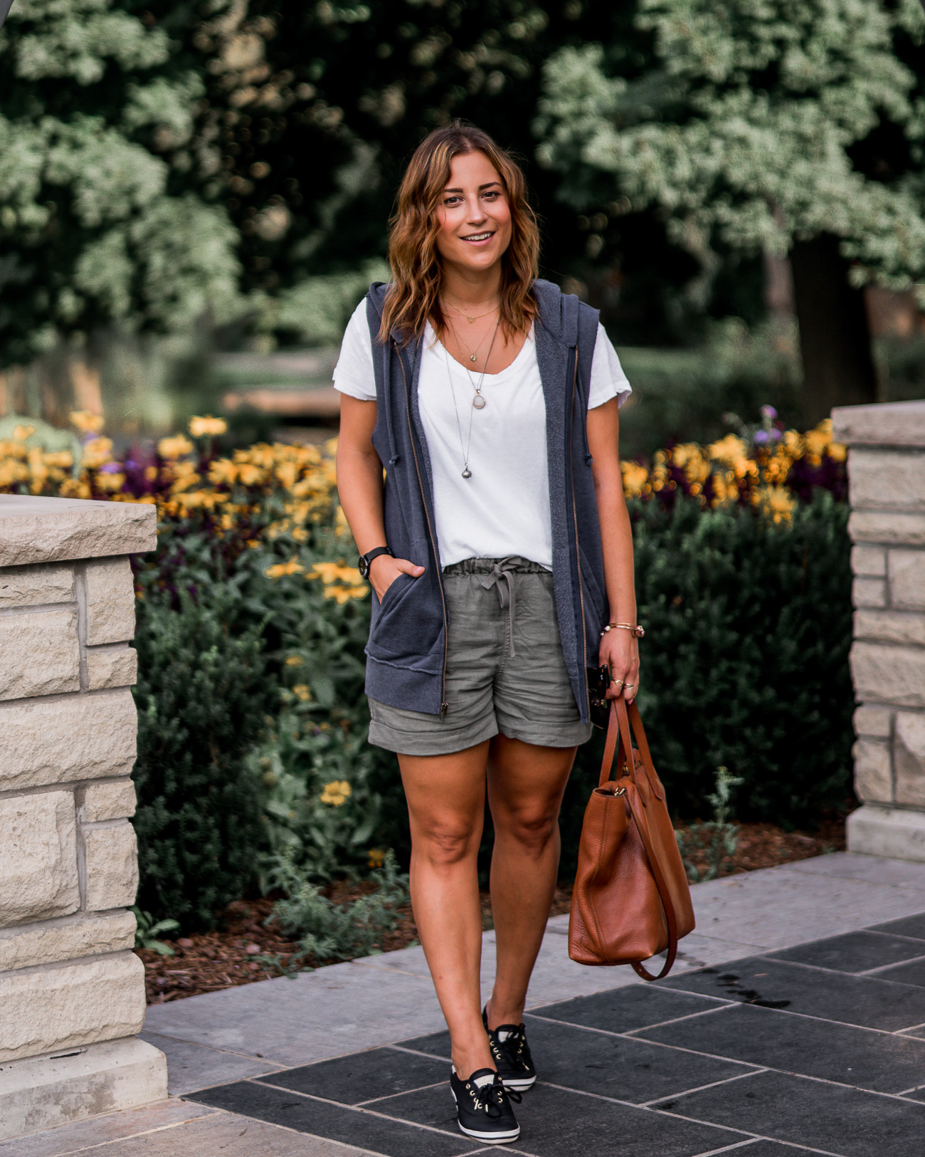 Toronto lifestyle and fashion blogger, Jackie Goldhar from Something About That, is wearing a late summer outfit, featuring a hoodie vest that will transition into fall